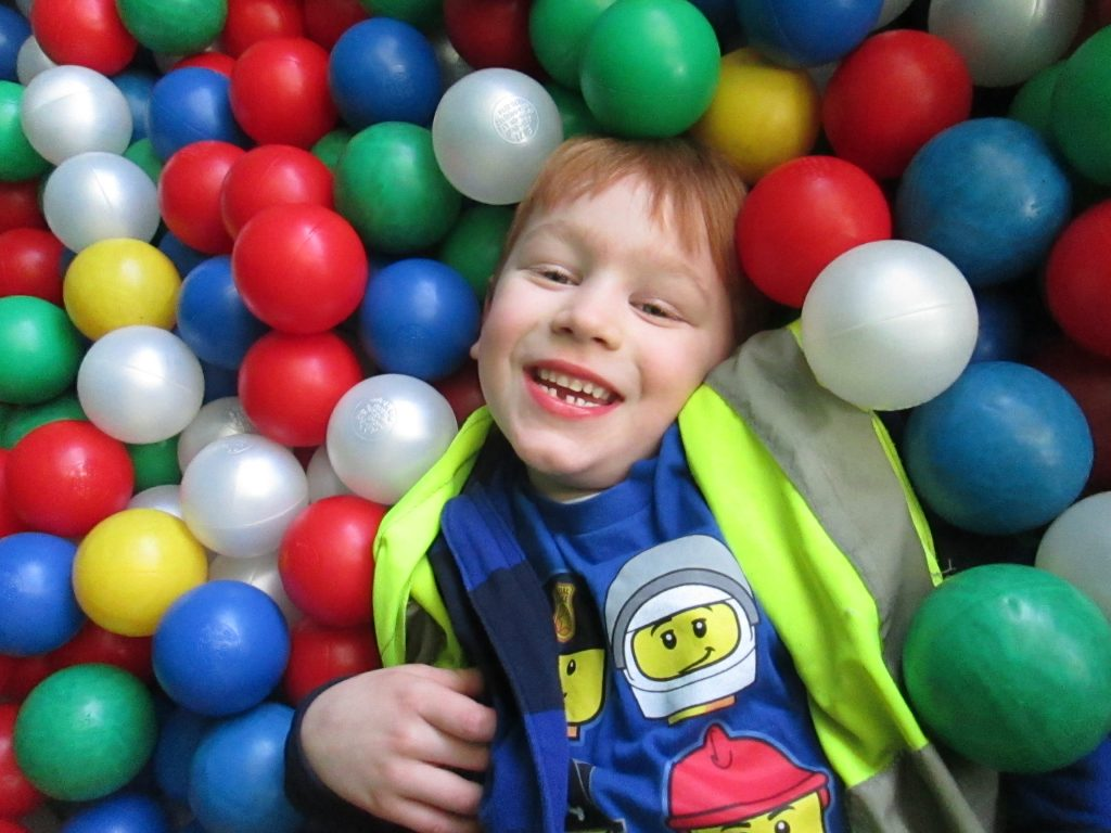 The Gower School boy smiling in a ball pit during Holiday Fun Club